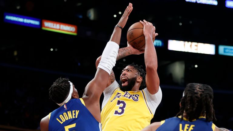 Los Angeles Lakers forward Anthony Davis (3) shoots against Golden State Warriors center Kevon Looney (5) during the first half of an NBA basketball game in Los Angeles, Tuesday, Oct. 19, 2021. (AP Photo/Ringo H.W. Chiu)