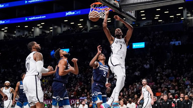 Brooklyn Nets' Kevin Durant (7) dunks in front of Minnesota Timberwolves' Jaden McDaniels (3) and Karl-Anthony Towns during the second half of a preseason NBA basketball game Thursday, Oct. 14, 2021, in New York. (AP Photo/Frank Franklin II)