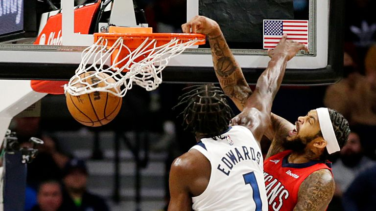 New Orleans Pelicans forward Brandon Ingram (14) dunks in front of Minnesota Timberwolves forward Anthony Edwards (1) in the second half of an NBA basketball game, Monday, Oct. 25, 2021, in Minneapolis.