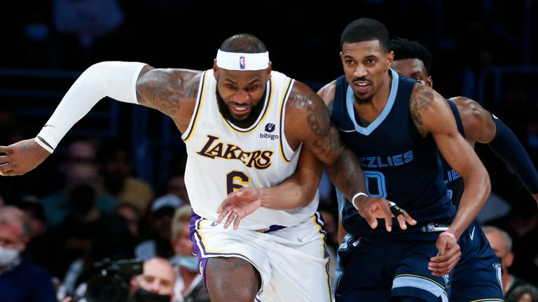 Los Angeles Lakers forward LeBron James (6) and Memphis Grizzlies guard De'Anthony Melton (0) chase the ball during the second half of an NBA basketball game in Los Angeles, Sunday, Oct. 24, 2021. The Lakers won 121-118.