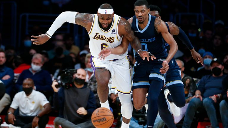 Los Angeles Lakers forward LeBron James (6) and Memphis Grizzlies guard De'Anthony Melton (0) chase the ball during the second half of an NBA basketball game in Los Angeles, Sunday, Oct. 24, 2021. The Lakers won 121-118. (AP Photo/Ringo H.W. Chiu)