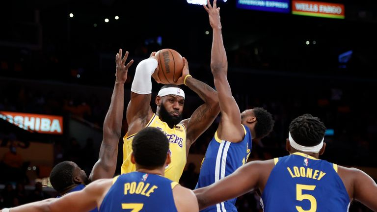 Los Angeles Lakers forward LeBron James, top left, looks to pass the ball against the Golden State Warriors during the first half of an NBA basketball game in Los Angeles, Tuesday, Oct. 19, 2021. (AP Photo/Ringo H.W. Chiu)