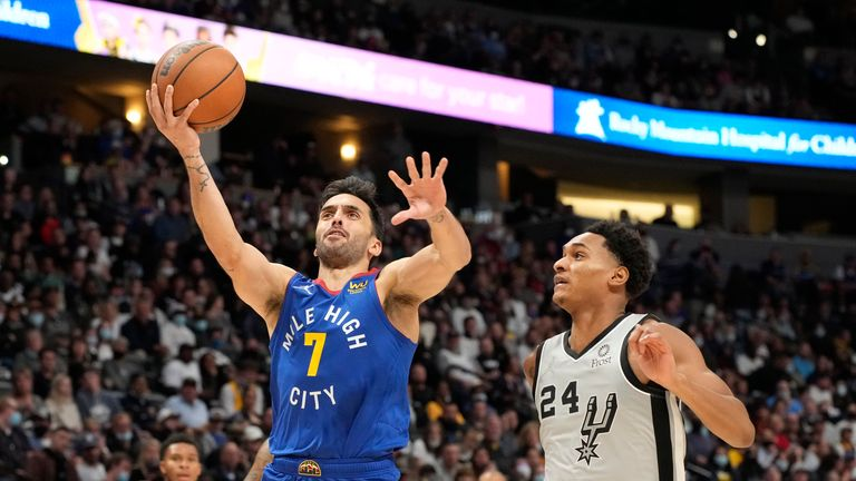 Denver Nuggets guard Facundo Campazzo, left, drives past San Antonio Spurs guard Devin Vassell during the second half of an NBA basketball game Friday, Oct. 22, 2021, in Denver. The Nuggets won 102-96. (AP Photo/David Zalubowski)