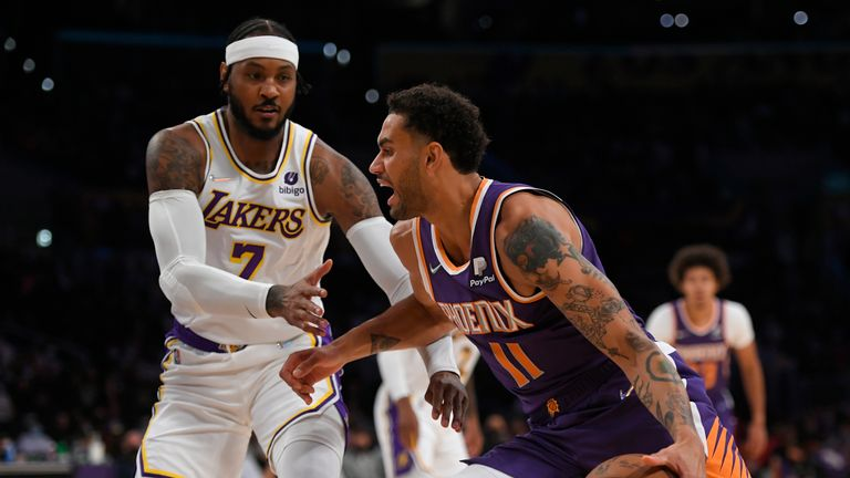 Los Angeles Lakers forward Carmelo Anthony (7) guards Phoenix Suns forward Abdel Nader (11) in the first half of a preseason NBA basketball game in Los Angeles, Sunday, Oct. 10, 2021. (AP Photo/John McCoy)