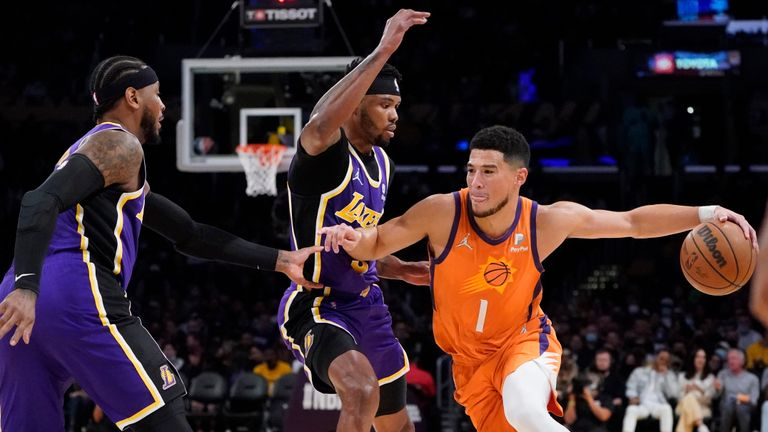 Phoenix Suns guard Devin Booker, right, is defended by Los Angeles Lakers forwards Kent Bazemore, center, and Carmelo Anthony during the first half of an NBA basketball game Friday, Oct. 22, 2021, in Los Angeles. (AP Photo/Marcio Jose Sanchez)