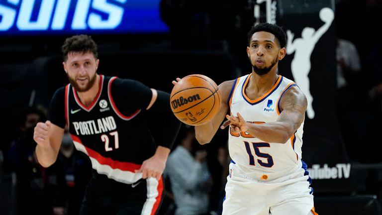 Phoenix Suns guard Cameron Payne (15) passes as Portland Trail Blazers center Jusuf Nurkic (27) pursues during the second half of a preseason NBA basketball game, Wednesday, Oct. 13, 2021, in Phoenix. (AP Photo/Matt York)