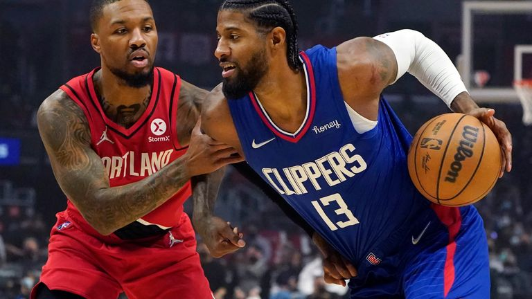 Los Angeles Clippers guard Paul George, right, is defended by Portland Trail Blazers guard Damian Lillard during the first half of an NBA basketball game Monday, Oct. 25, 2021, in Los Angeles.