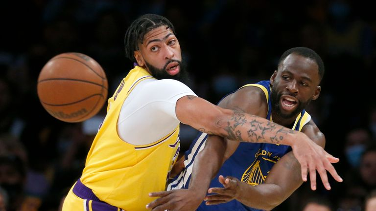 Golden State Warriors forward Draymond Green, right, passes the ball while defended by Los Angeles Lakers forward Anthony Davis during the first half of an NBA basketball game in Los Angeles, Tuesday, Oct. 19, 2021. (AP Photo/Ringo H.W. Chiu)