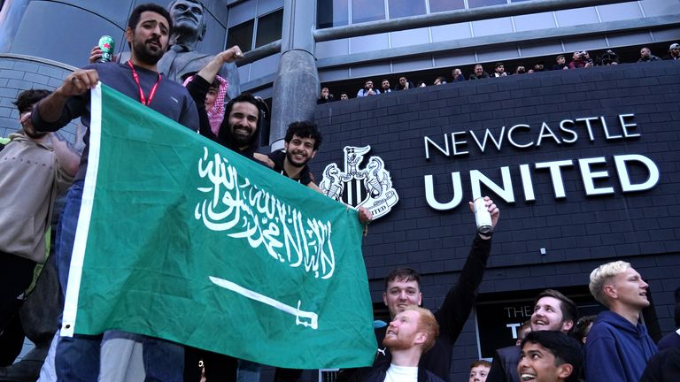 Newcastle fans celebrate after a Saudi-led consortium complete their takeover of the club