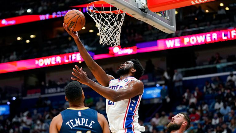 Philadelphia 76ers center Joel Embiid (21) goes to the basket over New Orleans Pelicans forward Garrett Temple (41) in the first half of an NBA basketball game in New Orleans, Wednesday, Oct. 20, 2021. (AP Photo/Gerald Herbert)