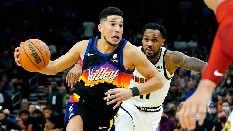 Phoenix Suns guard Devin Booker drives as Denver Nuggets guard Monte Morris, right, pursues during the second half of an NBA basketball game, Wednesday, Oct. 20, 2021, in Phoenix. (AP Photo/Matt York)
