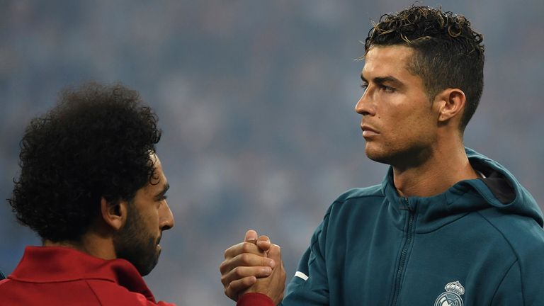 Madrid's Cristiano Ronaldo (R) and Liverpool's Mohamed Salah lock hands before the match