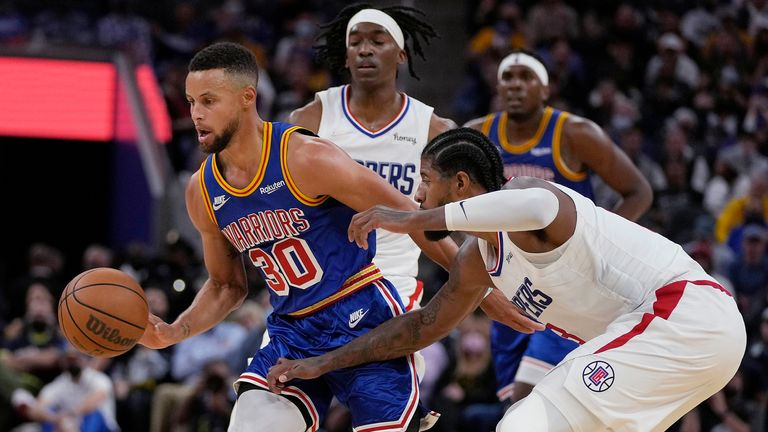 Golden State Warriors guard Stephen Curry dribbles around Los Angeles Clippers guard Paul George